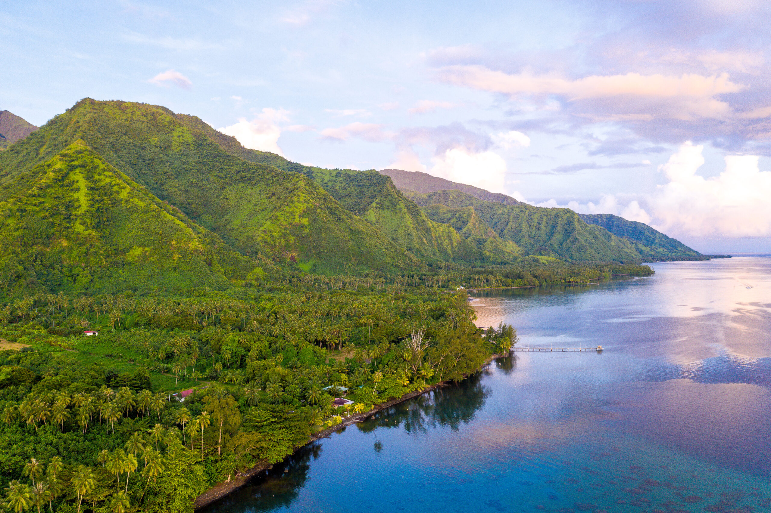best drone shots taken by Ashley in Tahiti. Split show, on the left the tall volcanic walls of tahiti covered in many shades of green and on the right the incredible ocean with blues and pinks from the sunset reflecting off of the water