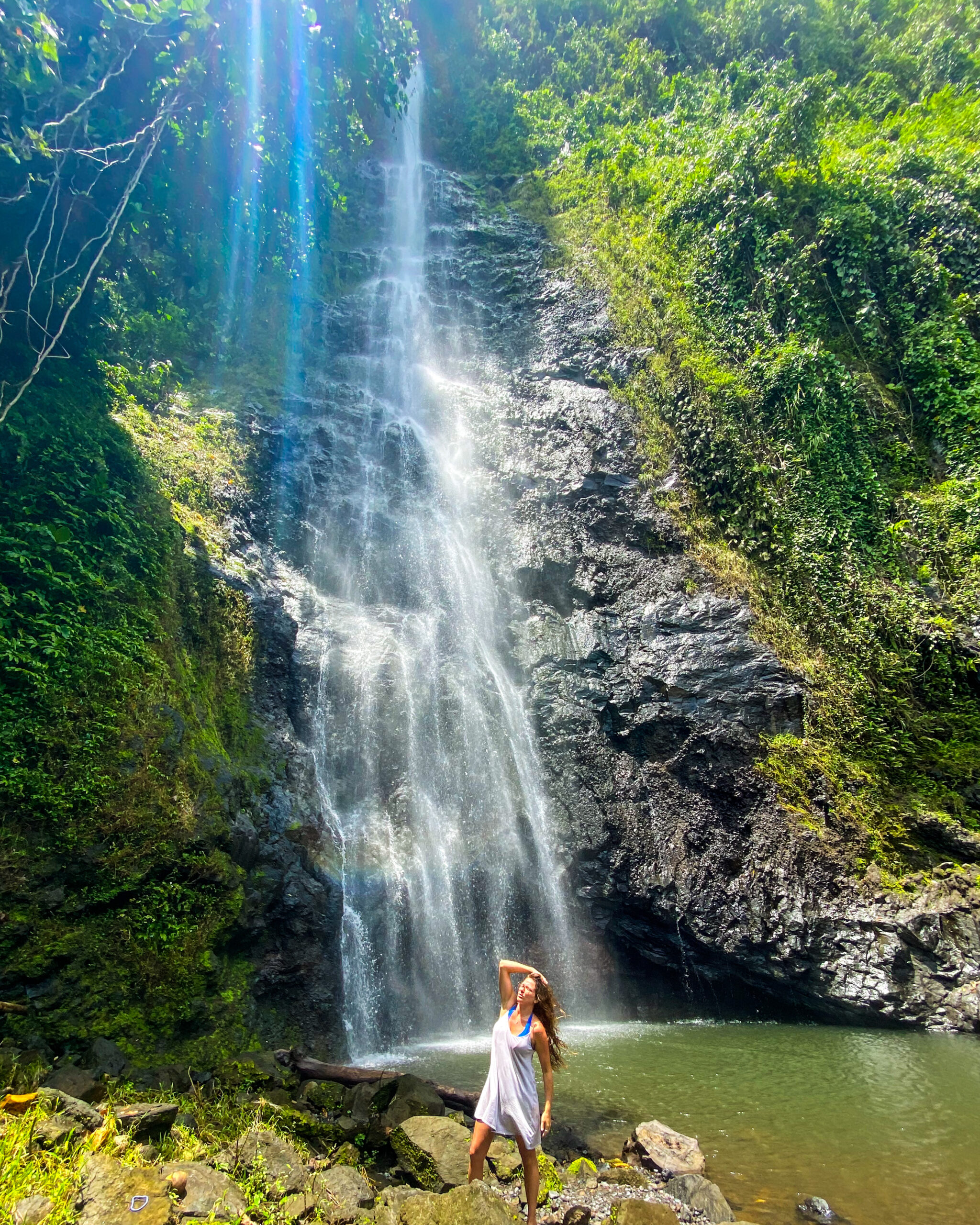 girl in a gray dress on the island of Moorea standing in front of beautiful waterfall