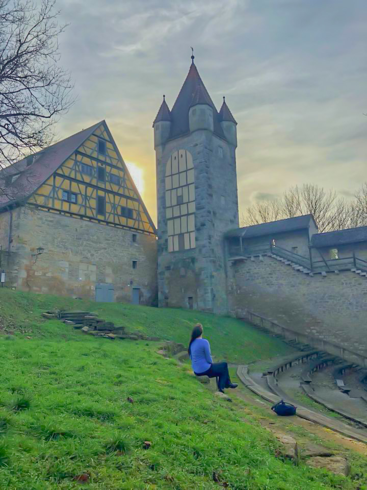 a girl in a blue shirt and black pants exploring the City wall in Rothenburg ob der Tauber, Germany